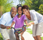 happy family with daughter playing a bike